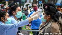 Health officials, wearing face masks amid fears over the spread of the COVID-19 novel coronavirus, check the body temperature of policewomen before an anti-government rally in Bangkok on March 1, 2020. (Photo by Mladen ANTONOV / AFP) (Photo by MLADEN ANTONOV/AFP via Getty Images)