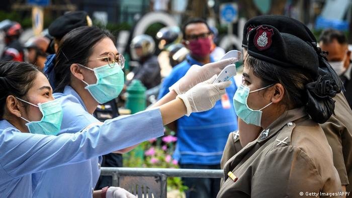 Health officials wearing face masks check the body temperature of policewomen before a rally in Bangkok on March 1
