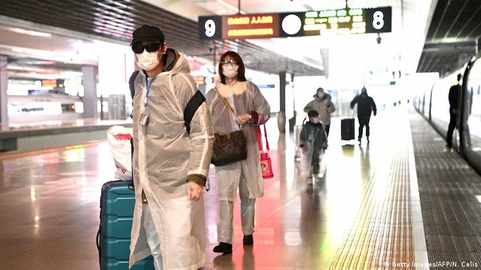 People go through airport wearing masks and protective clothing during pandemic