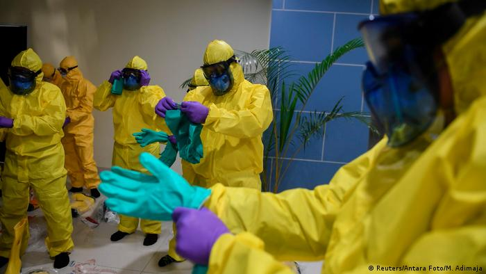 Officials in protective suits prepared to check Indonesian evacuees from the Diamond Princess cruise ship.