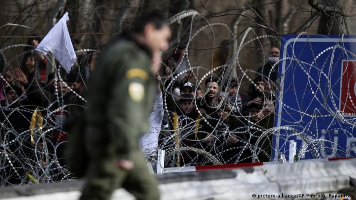 Migrants stand behind a fence near the Kastanies border gate at the Greek-Turkish border
