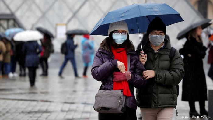A couple wears medical face masks outside the Louvre Museum in Paris