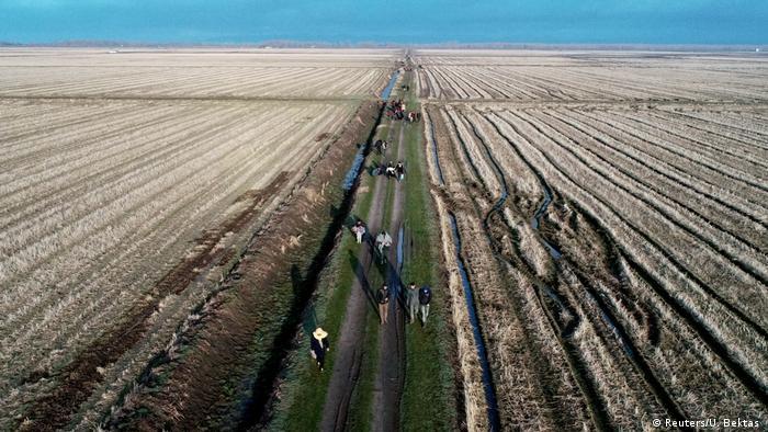 Imagem aérea mostra estrada de terra em meio a campo cultivado. Imigrantes caminham em direção ao horizonte, rumo à Grécia, a partir da Turquia