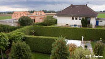 Ein Haus mit einem Garten und großen Bäumen