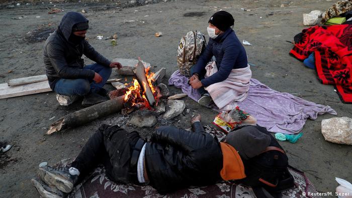 Migrants sit on a road side near Turkey's Ipsala border crossing with Greece