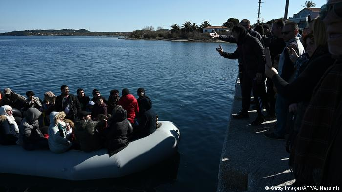 Refugees on a boat watch locals try to stop them from disembarking in Lesbos