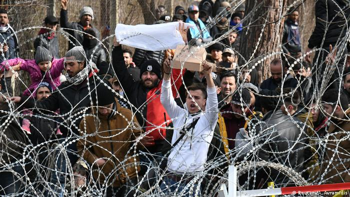 Migrants who want to cross into Greece from Turkey's Pazarkule border crossing shout slogans behind rolls of barbed wire