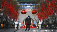 16.02.2020, China, Peking: Ein Sicherheitsmann mit Mundschutz geht durch die Menschenleere Hauptstraße Qianmen, normalerweise ein beliebter Touristenort. Die Zahl der Infektionen und Todesfälle durch das Coronavirus ist in China erneut gestiegen. Foto: Andy Wong/AP/dpa +++ dpa-Bildfunk +++ |