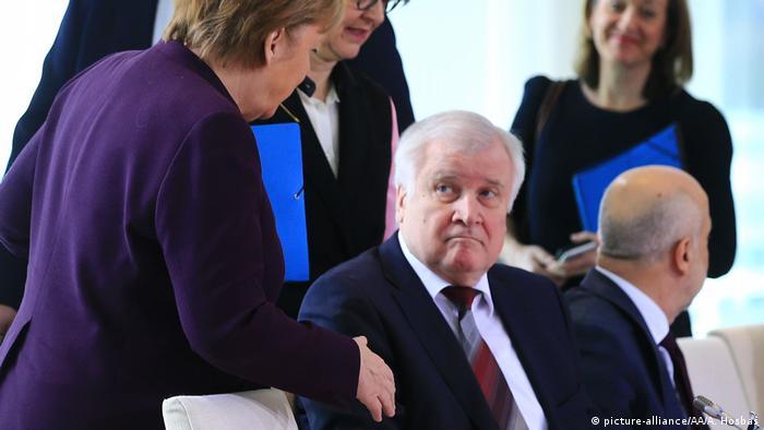 Merkel, de pie, extiende su mano a Seehofer.