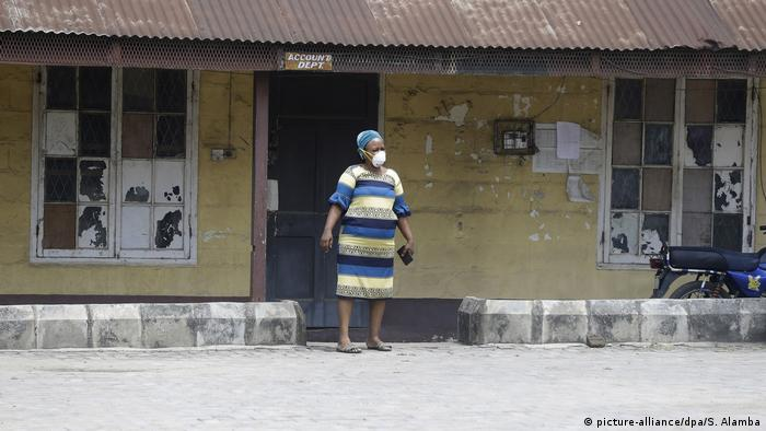 A woman wearing a surgical mask stands outside a building in Lagos (picture-alliance/dpa/S. Alamba)