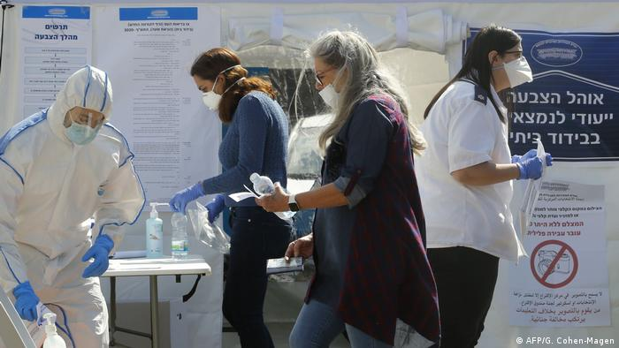 Voters head to the polls wearing facemasks