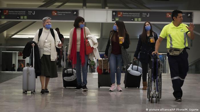 Foto de personas con maletas y mascarillas en el Aeropuerto de México