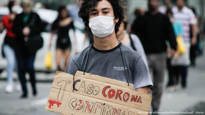 Jovem com máscara segura cartaz: Primeiro caso corona confirmado