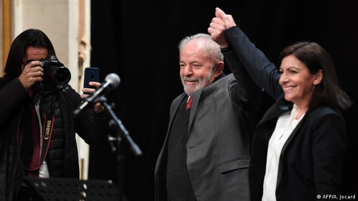 Ao centro, vestindo terno cinza e gravata vermelha, ex-presidente Lula ergue o braço junto com a prefeita de Paris, Anne Hidalgo (c.), por ocasião de cerimônia em que recebeu título de cidadão honorário da capital francesa