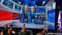 This picture taken on March 2, 2020 shows people standing before a giant screen displaying a broadcast from Israel's Channel 13 with an exit poll prediction after polls closed in the Israeli elections, predicting that Prime Minister Benjamin Netanyahu's Likud party wins 37 seats against 32 for Benny Gantz' Blue and White (Kahol Lavan) electoral alliance, at the Blue and White's headquarters in the coastal city of Tel Aviv. (Photo by MENAHEM KAHANA / AFP)