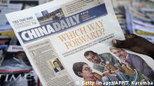 A newspaper consumer reads a copy of China's Africa edition of its daily newspaper infront of a news stand in the Kenyan capital on December 14, 2012. China today launched an African edition of its China Daily newspaper, the latest media venture by Beijing on the continent. The relationship between China and the African continent is one of the most significant relationships in the world today, publisher and editor-in-chief of the state-run paper Zhu Ling wrote in the inaugural copy. AFP PHOTO/Tony KARUMBA (Photo credit should read TONY KARUMBA/AFP via Getty Images)