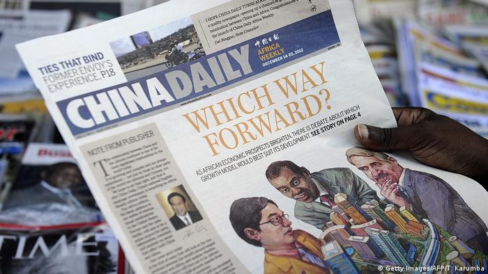 A newspaper consumer reads a copy of China's Africa edition of its daily newspaper infront of a news stand