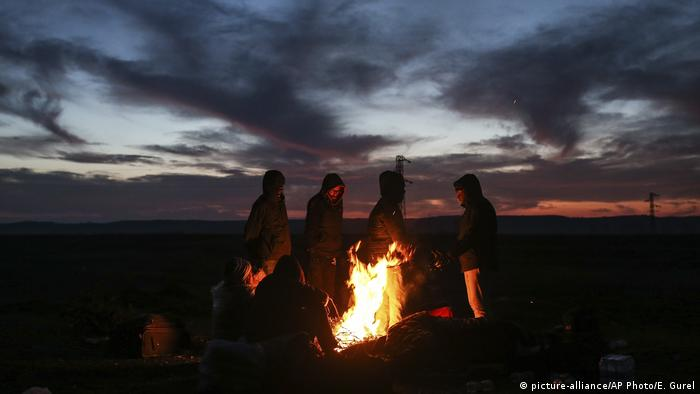 Migrants stand around a bonfire as they try to warm themselves in Edirne, Turkey