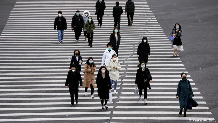 People cross the street wearing masks