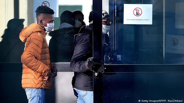 Students and their parents wearing face masks arrive at the Jean-de-la-Fontaine school in Crepy-en-Valois, northern France, while tests are carried out on March 3, following the death of a 60-year-old teacher who worked at the school.