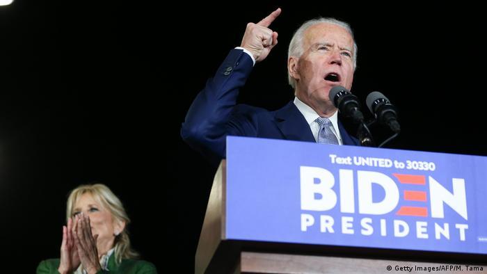 Pré-candidato à presidência dos EUA Joe Biden discursa em evento de campanha atrás de púlpito ornado com os dizeres Biden Presidente