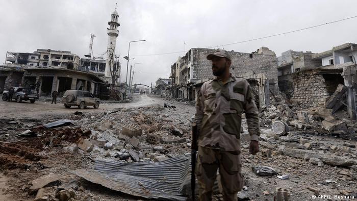 Военный сирийской армии на фоне разрушенных зданий в провинции Идлиб