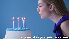 Frau bläst Kerzen auf Geburtstagstorte aus