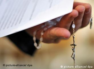 A hand with a rosary and prayer sheet