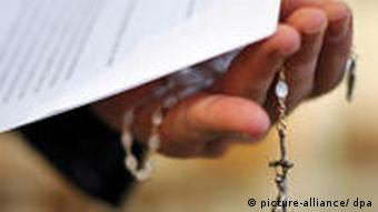 A priest holding a rosary and a report documenting abuse at the Jesuits