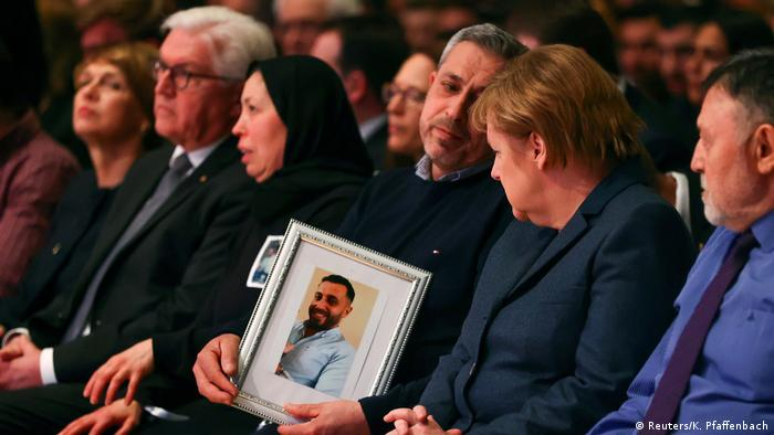 Germany's Chancellor Angela Merkel looks at the picture of a victim of the shootings in Hanau as she attends the memorial service for the victims of the shootings in Hanau, Germany, March 4, 2020.