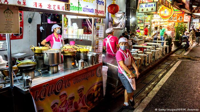 Street-food sellers wear facemasks on an otherwise deserted street in Bangkok's Chinatown