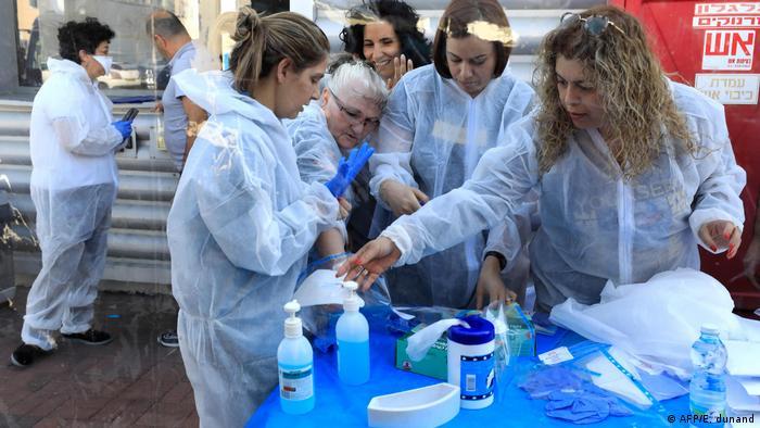 Волонтеры в защитных костюмах на выборах в Израиле