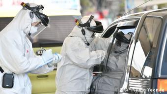Pessoas com roupa anticontaminação recolhem teste de motorista dentro de carro