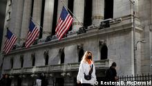 FILE PHOTO: A woman wears a mask near the New York Stock Exchange (NYSE) in the Financial District in New York, U.S., March 4, 2020. REUTERS/Brendan McDermid - RC28DF9HJ2FQ/File Photo
