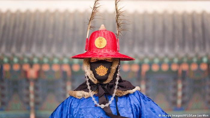 An official wearing a mask and a traditional guard uniform stands at Gyeongbokgung Palace in Seoul