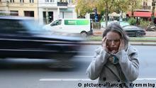 Spannungskopfschmerzen und Migräne. Junge Frau mit Migräne und Spannungskopfschmerz steht am Straßenrand und hält sich die vor Schmerzen die Hände an den Kopf. Verkehrslärm als Auslöder von Migräne. 03.11.2017 | Verwendung weltweit