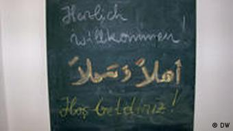 A blackboard, with text in German, Turkish and Arabic