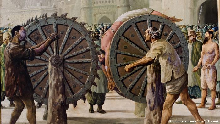 Historisches Gemälde zur Foltermethode des Räderns: Ein Mann ist auf ein Rad gebunden. Im Hintergrund steht eine Menschenmenge und schaut zu.