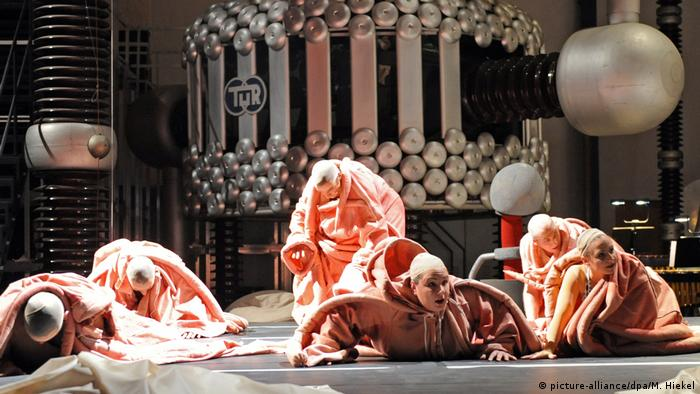 people in apricot-colored costumes hovering on a stage (Foto: picture-alliance/dpa/M. Hiekel).