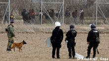 Greece's riot police officers stand guard and a soldier walks with a dog as migrants gather at the borderline near the Turkey's Pazarkule border crossing, in Kastanies, Greece March 4, 2020. REUTERS/Florion Goga
