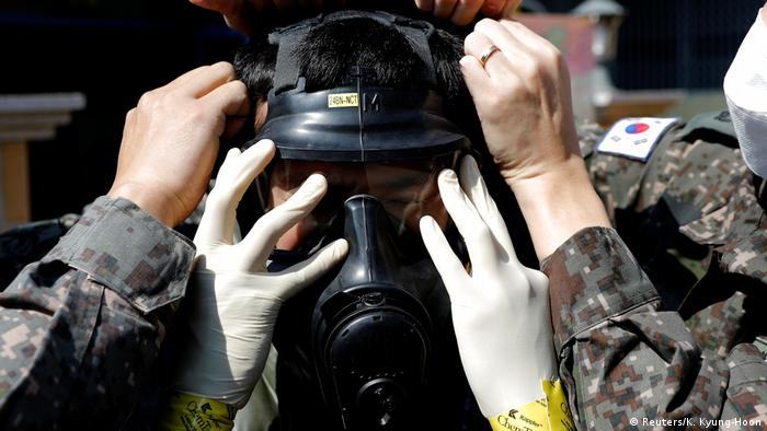 A South Korean solider puts on protective gear with help from his colleagues as prepares for quarantine work