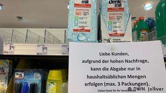 Дезинфицирующие салфетки на полке галантереи dm в Берлине и объявление об отпуске только трех упаковок в одни руки.