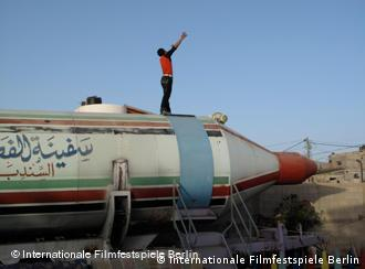 Still from the documentary 'Still alive in Gaza' showing young man standing on a rocket with his arms up in the air