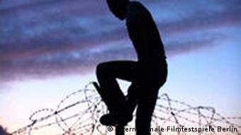 Man climbing barbed-wire fence