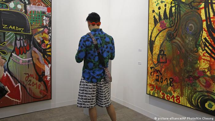 A visitor looks at paintings created by German artist Jonathan Meese at Art Basel in Hong Kong in 2019