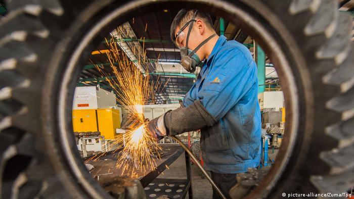 Trabalhador numa fábrica opera equipamento que produz faísca