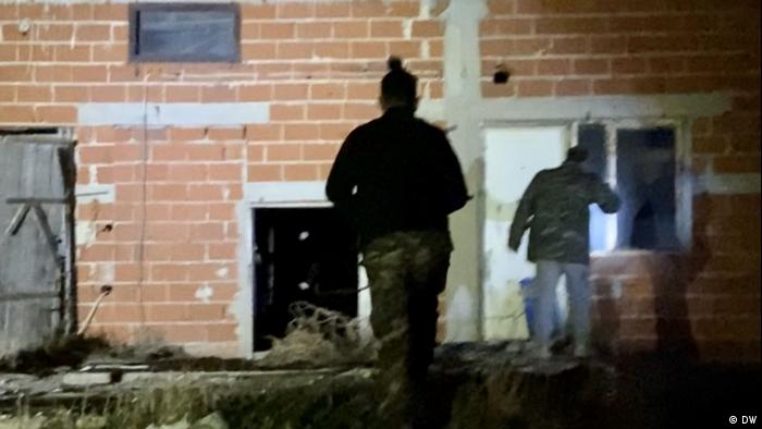Members of the National Guard in front of a vacant house