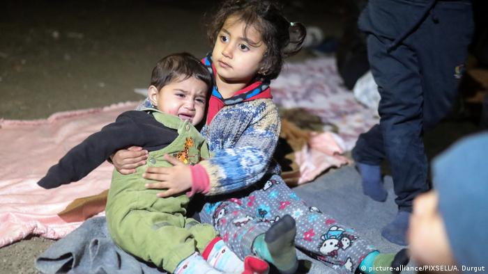 Young refugees sit on the ground
