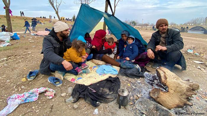 Izbjeglice na ledini, uz provizorni šator koji su sami napravili