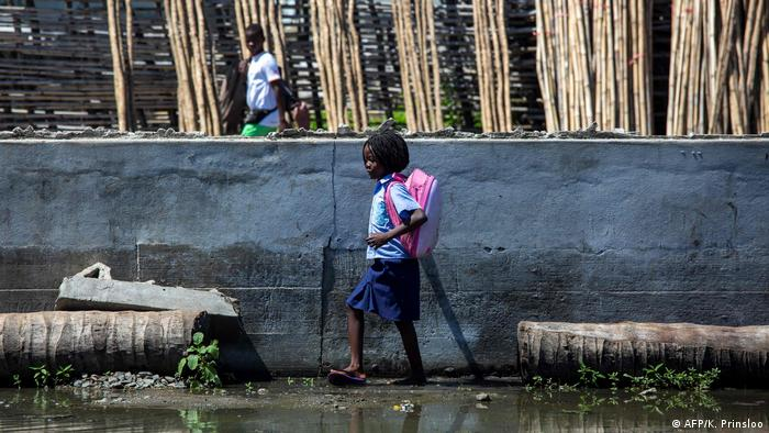 A schoolchild in Beira, Mozambique, walking across a flooded schoolyard